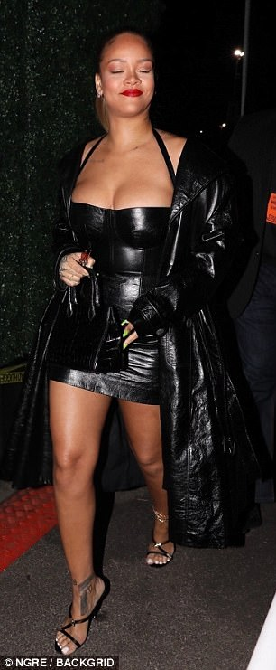 All eyes on her: Rihanna, 29, dressed to impress in her black leather mini, with the halter-neck design highighting her ample assets which threatened to spill out of the low-cut dress