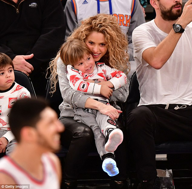 Tender moment: Shakira cuddled her two-year-old son Sasha at the game