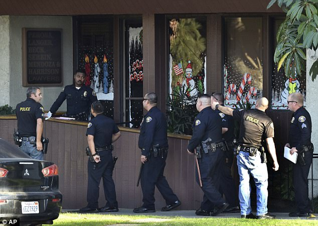 There were three men involved, two of whom were killed, including Mendoza, according to police.  Pictured is the building, believed to house law offices, with windows covered in Christmas displays featuring candy canes and Santa Clause