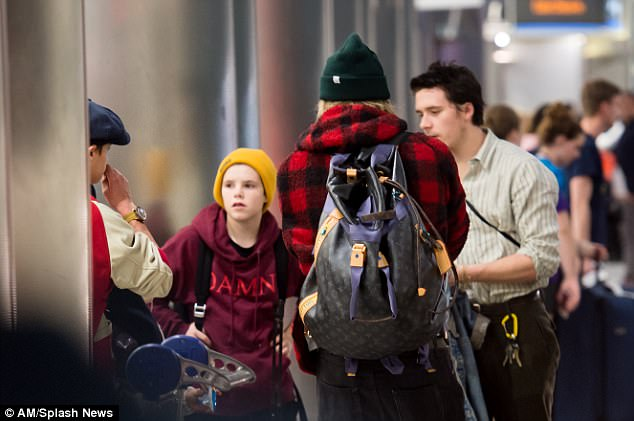 Deep in discussion: The family looked tired as they arrived at the airport following their long-haul flight