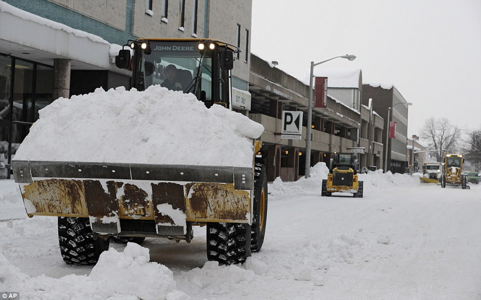 Workers clear streets on Friday in downtown Erie. Sixty-five inches of snow fell on the city over the course of four days