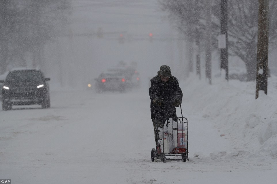A man walks with his groceries in a cart on Friday in Erie. The cold weather pattern is expected to continue through the holiday weekend and likely longer