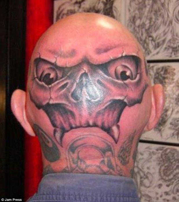 La brillante calva roja de este hombre hace que el tatuaje de su cara de calavera sea aún más aterrador, y los colmillos lo vuelven más loco