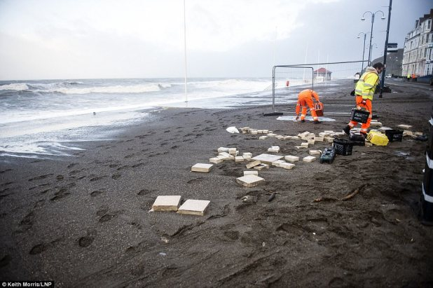Workers on the beachfront in Aberystwyth work to restore the anguish introduced about by the Storm Eleanor
