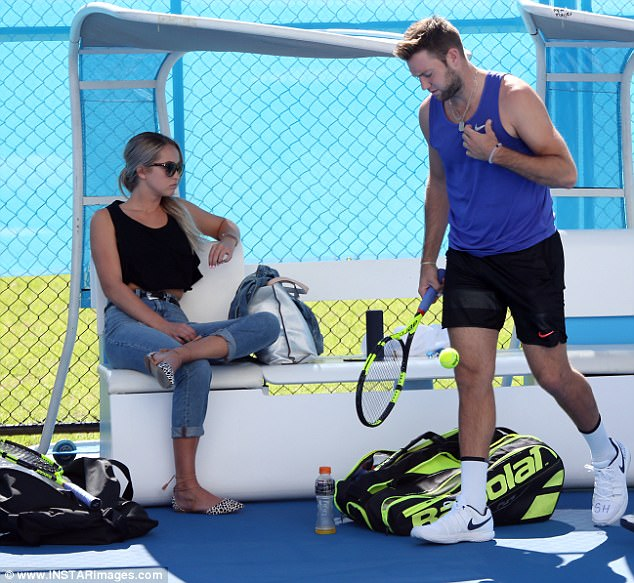 Better places to be? American tennis player Jack Sock trains in Perth while his girlfriend Michala Burns looks bored on the sidelines on Thursday