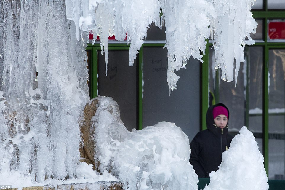 A woman passes an ice-covered fountain in New York's Bryant Park on Friday