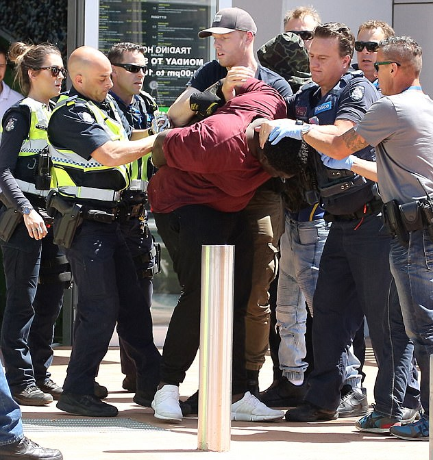 A teenager is restrained by several police outside Tarneit Central shopping centre during a series of violent confrontations which resulted in three arrests on Wednesday afternoon