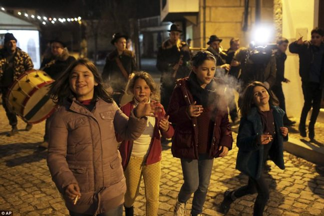 Children smoke while walking with a music band in the village of Vale de Salgueiro, northern Portugal, during the local Kings' Feast