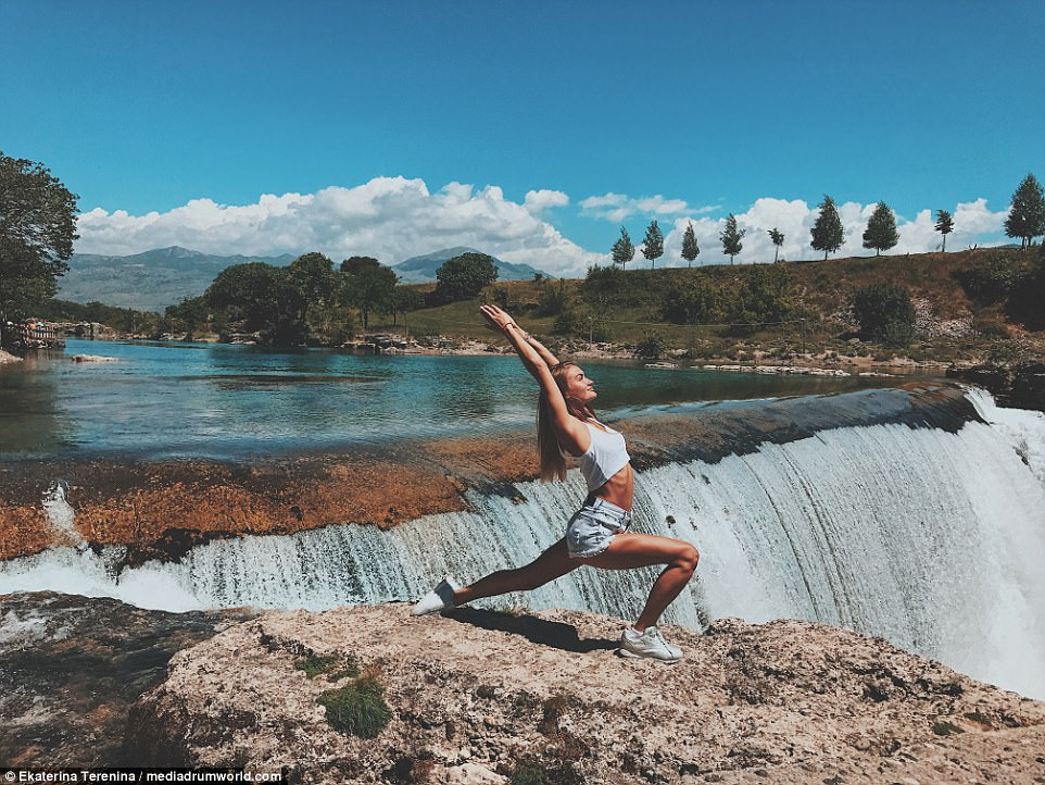 Working out in Montenegro: The brunette beauty showcases her flexibility while stood before a huge waterfall