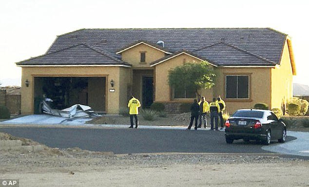 Investigators stand outside the home of Stephen Paddock on October 2. Thesearch found 19 guns and several pounds of potentially explosive materials, police said