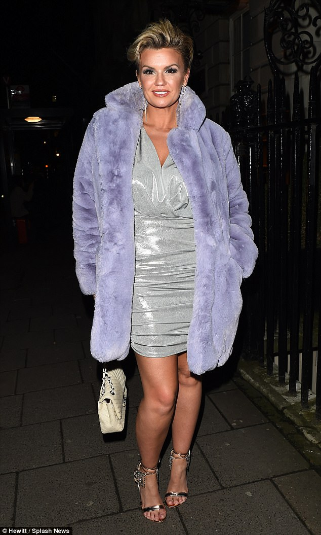 Glam: The 37-year-old star oozed confidence as she paraded her toned physique in a plunging silver mini dress and furry purple coat