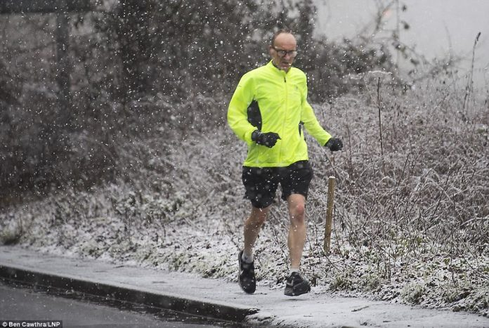 One man braves the cold in just a jacket and shorts this morning to take a run as snow falls in Maidenhead, Berkshire