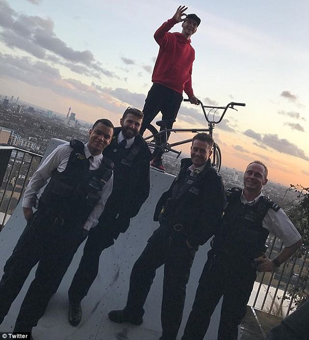Ryan Taylor, who boasts 674,000 subscribers, poses with police officers after building a ramp on a penthouse balcony in one of his stuns