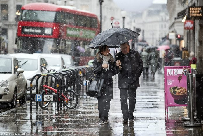 Shoppers shield themselves from the snow as they walk along Oxford Street this afternoon, as wintry conditions hit London