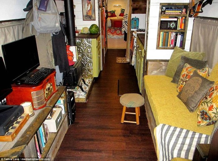 Relatively spacious: Inside, the mobile home also boasts a sofa, TV and computer access, plus a wood-burning fire