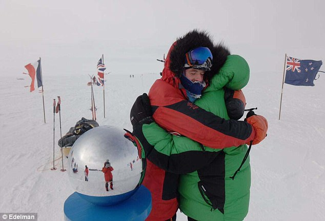 Robert and Barney Swan are pictured hugging at the South Pole, next to the silver sphere in which Barney saw his reflection for the first time in weeks