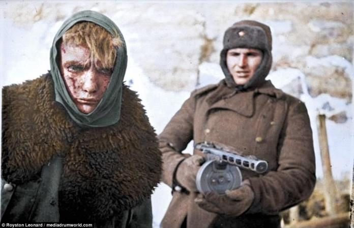 A Russian soldier, armed with a PPSh-41 submachine gun, stands guard over wounded German solider. The down-trodden prisoner-of-war has a bloodied face. The photo, originally from the German Federal Archive is thought to have been taken in January 1943, in the final weeks of the Stalingrad onslaught