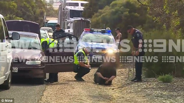 The footage was captured near the Murray Bridge just after 10am. Police can be seen closing in on a 90s Holden Commodore, with one man lying prone on the ground