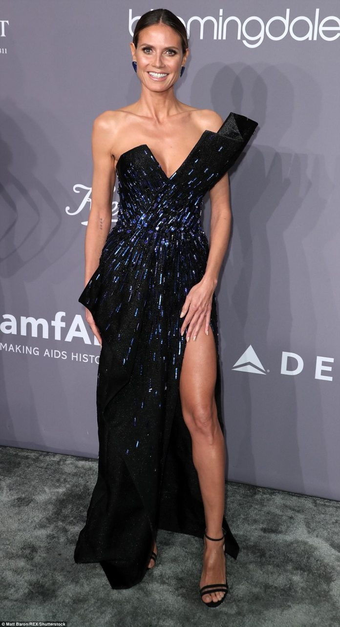 Heidi, 44, opted for a dramatic gown slit to the thigh and with a plunging neckline.She paired it with matching sandal heels and stunning earrings