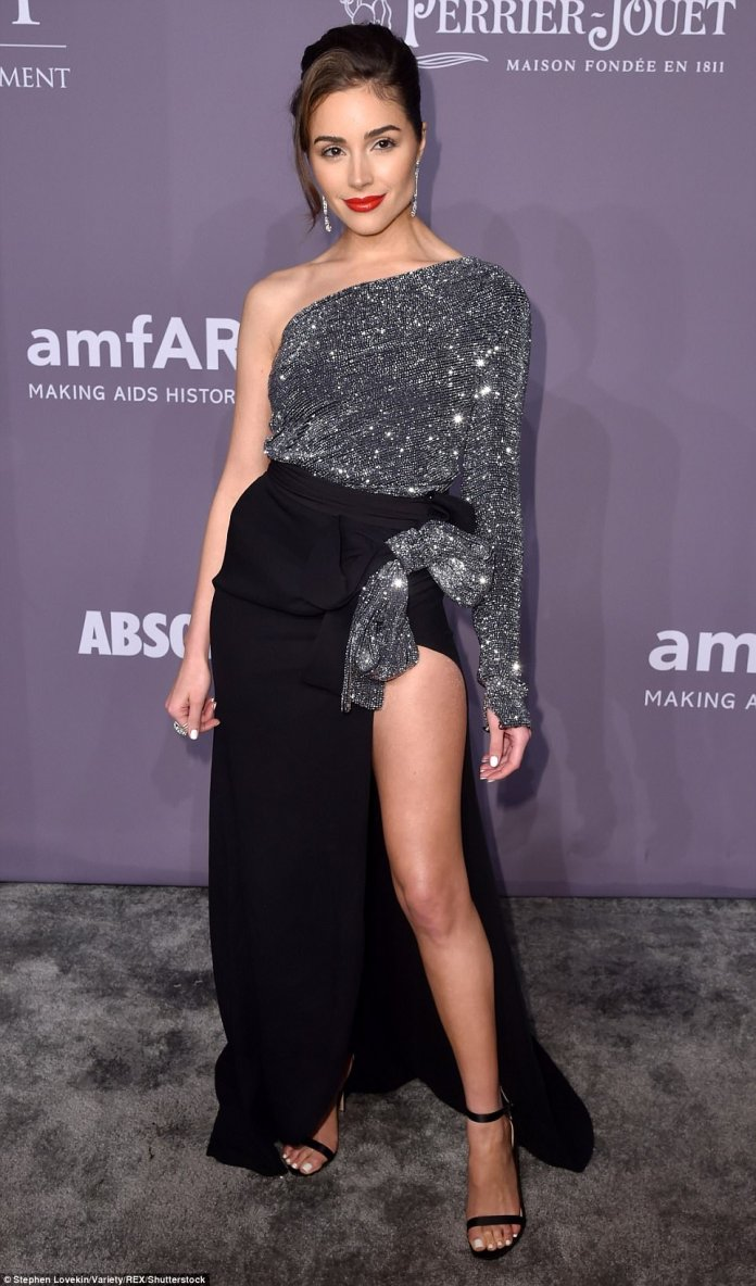 Olivia, 25, chose a two-tone outfit that paired a silver sparkly one-shoulder top with a trailing black skirt slit to the thigh on one side and a silver sparkly bow at the hip