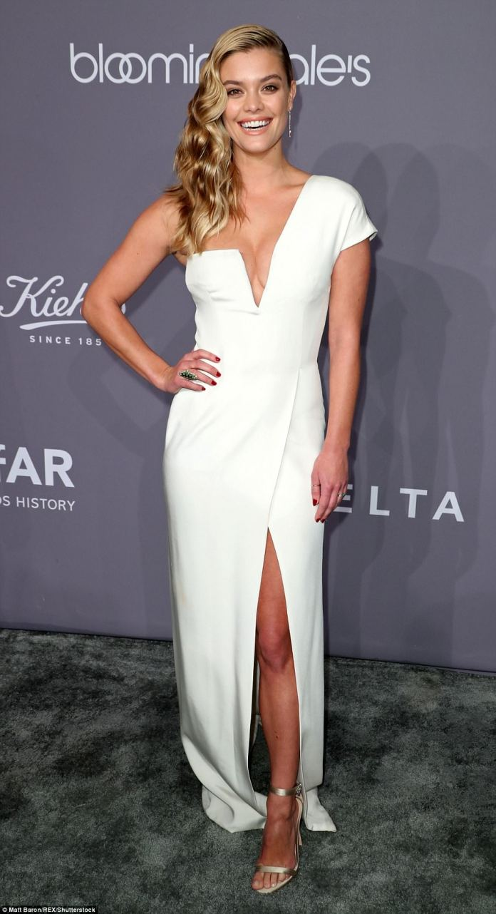 Nina Agdal, 25, showed off her curves in a one-shoulder white dress with a very plunging neckline that she paired with silver sandal heels