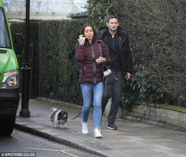 Puppy love: Former footballer Frank, 39, matched his wife's look in a black padded parka and trainers, while keeping the couple's pet pooch Minnie close