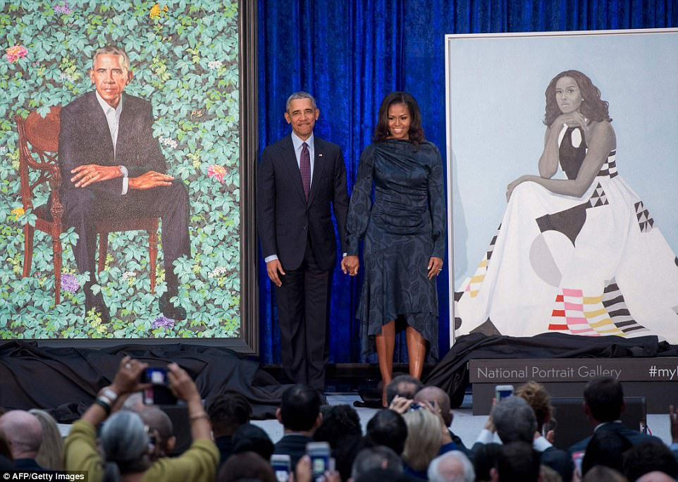 Former US President Barack Obama and First Lady Michelle Obama stand beside their portraits after their unveiling at the Smithsonian's National Portrait Gallery in Washington, DC, on Monday