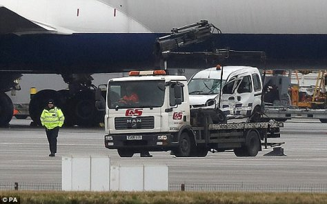 One of the vehicles involved in a crash at Heathrow Airport is removed from the scene today
