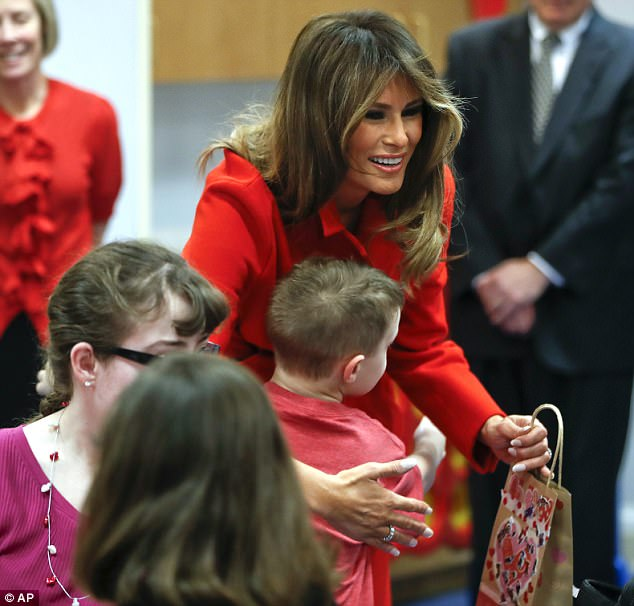Melania gave a little boy wearing a red T-shirt a big hug during her visit