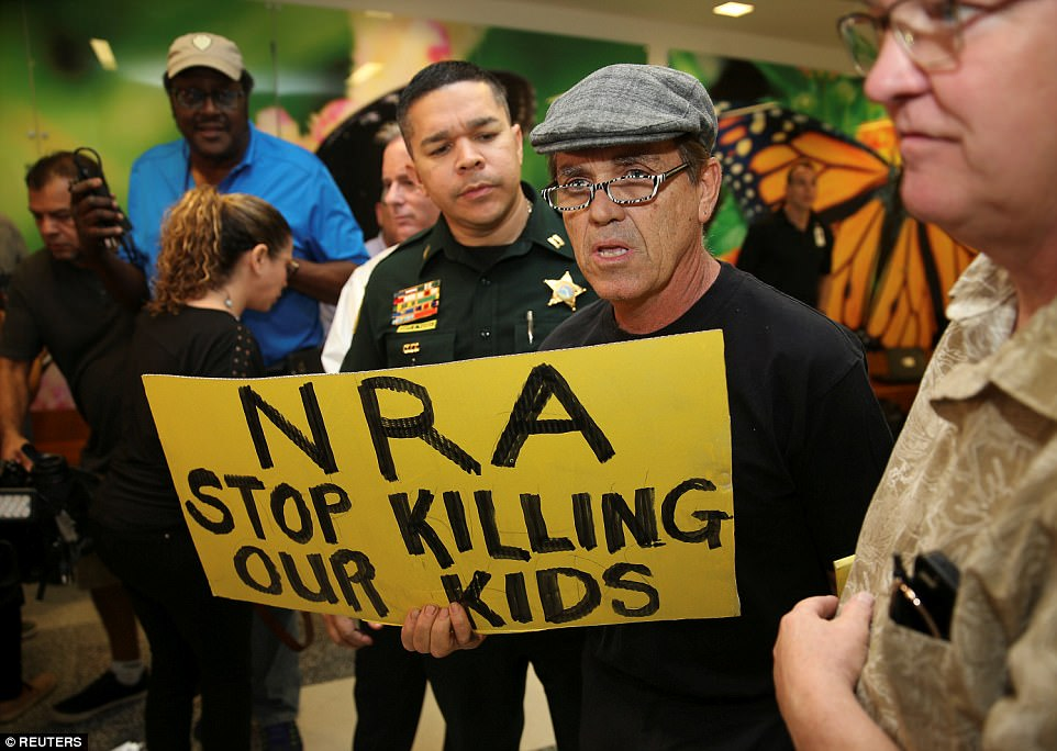 A man with a sign is seen after the news conference in the hallway outside the courtroom where Nikolas Cruz appeared via video at a bond court hearing after being charged with 17 counts of premeditated murder, in Fort Lauderdale, Florida, U.S., February 15, 2018