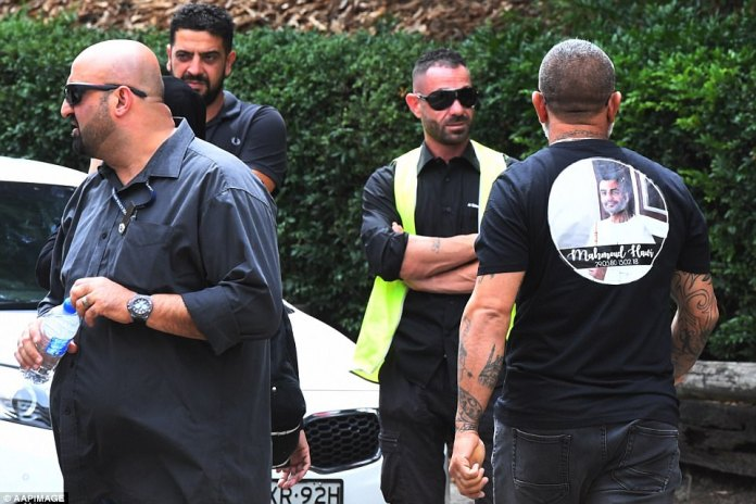 Up to 200 mourners, many dressed in black tribute t-shirts with Hawi's face and name on the back (right), were seen piling into the mosque