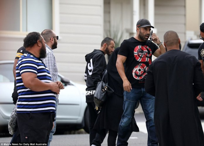 One man, dressed in a Gucci shirt with an eye catching snake logo, appeared to be having a heated conversation on the phone ahead of Hawi's memorial