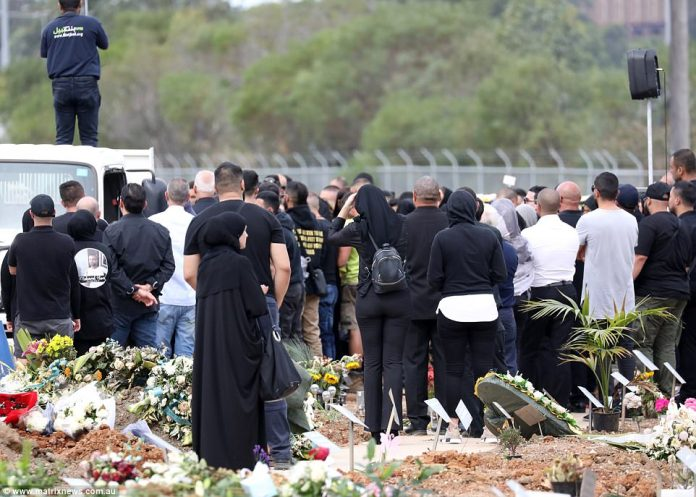 Flowers are seen covering the ground around the father-of-two's burial site as mourners pay their respects on Thursday