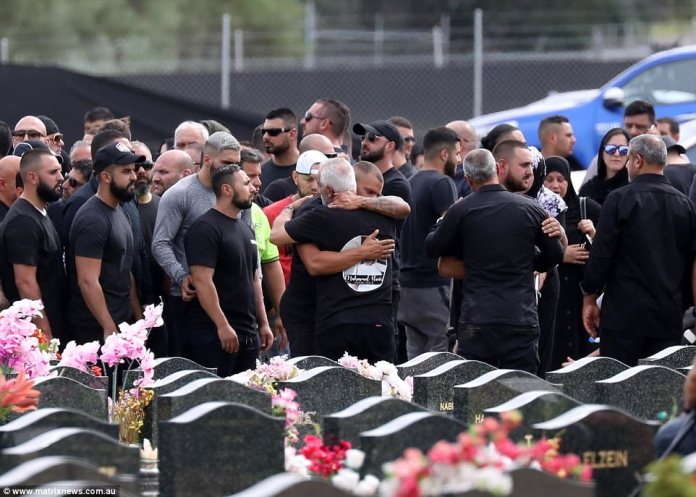 Mourners comfort one another after former Comanchero president Hawi is buried in Sydney on Thursday afternoon