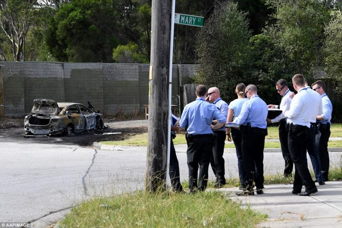 Police gather near a burnt out car which they believe was the getaway vehicle after a shooting in Melbourne