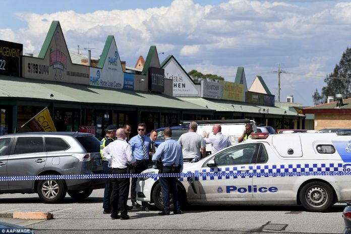 Victoria police officers monitor the scene of a shooting at a tattoo parlour in Hampton Park in Melbourne on Thursday