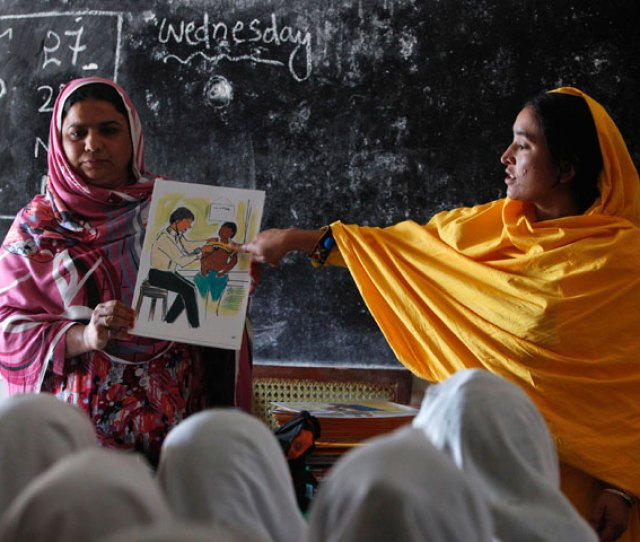 Teachers Display A Card With An Illustration Depicting A Girl Going Through A Medical Checkup By