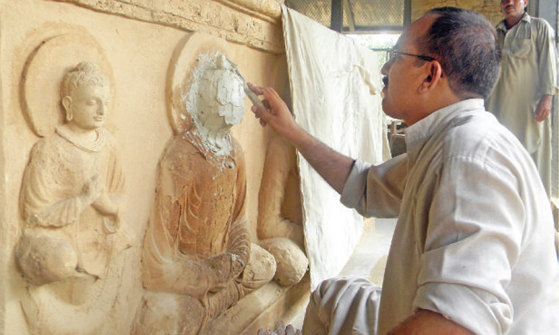 A worker reconstructs the face of Buddha at the Jaulian stupa. — Dawn
