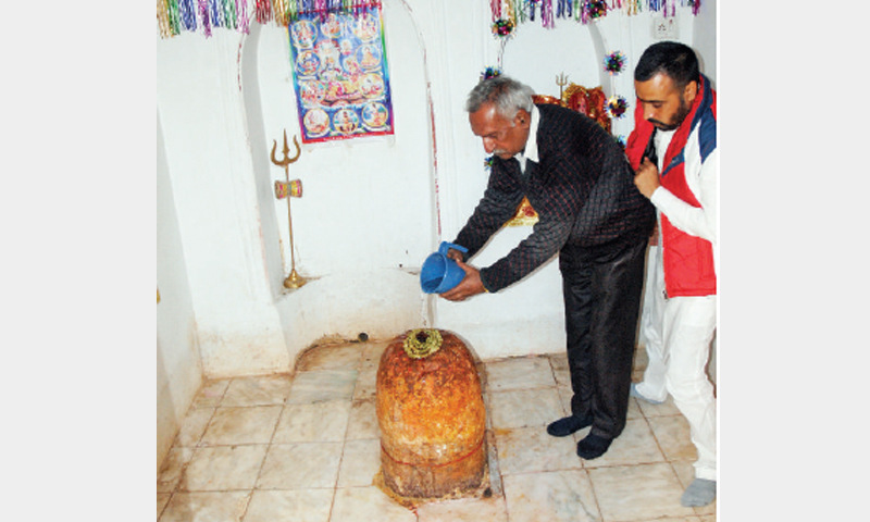 Hindu pilgrims perform rituals at the Linga Stone at Katas Raj. — Dawn