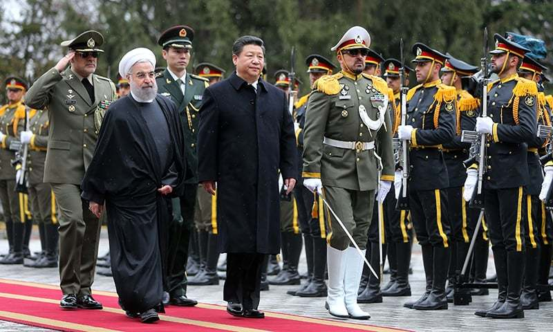 Chinese President Xi Jinping reviews an honor guard as he is welcomed by his Iranian counterpart Hassan Rouhani. AP