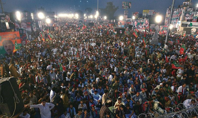 PTI supporters sit on the road to listen to Imran Khan's speech at Raiwind — White Star