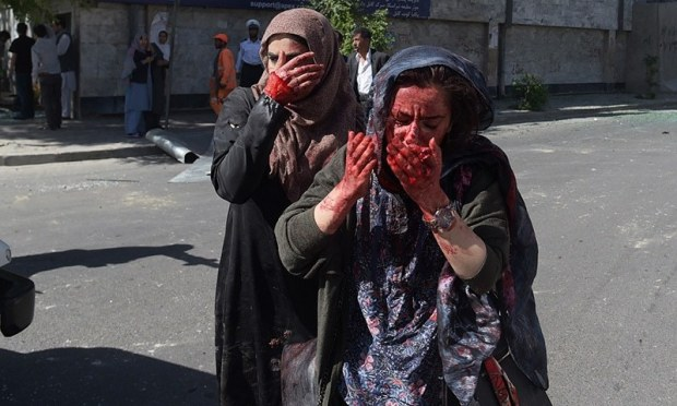 Wounded Afghan women gesture at the site of a car bomb attack in Kabul on May 31, 2017.— AFP