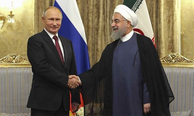Iran's President Hassan Rouhani shakes hands with Russian President Vladimir Putin during their meeting at the Saadabad Palace.─AP
