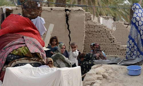 A family of Pakistani earthquake survivorss sit with their belongings near their collapsed mud houses in the Mashkail area of southwest Baluchistan province. - Photo by AFP