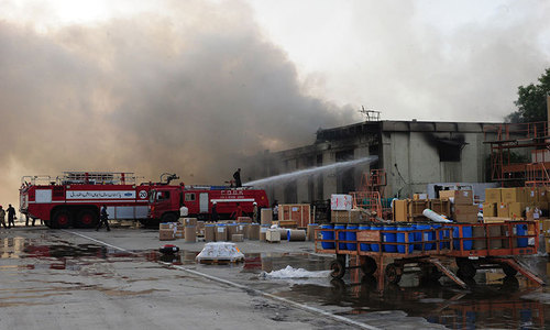 Firefighters extinguish fires after militants attack Jinnah International Airport in Karachi on June 9, 2014. — Photo by AFP