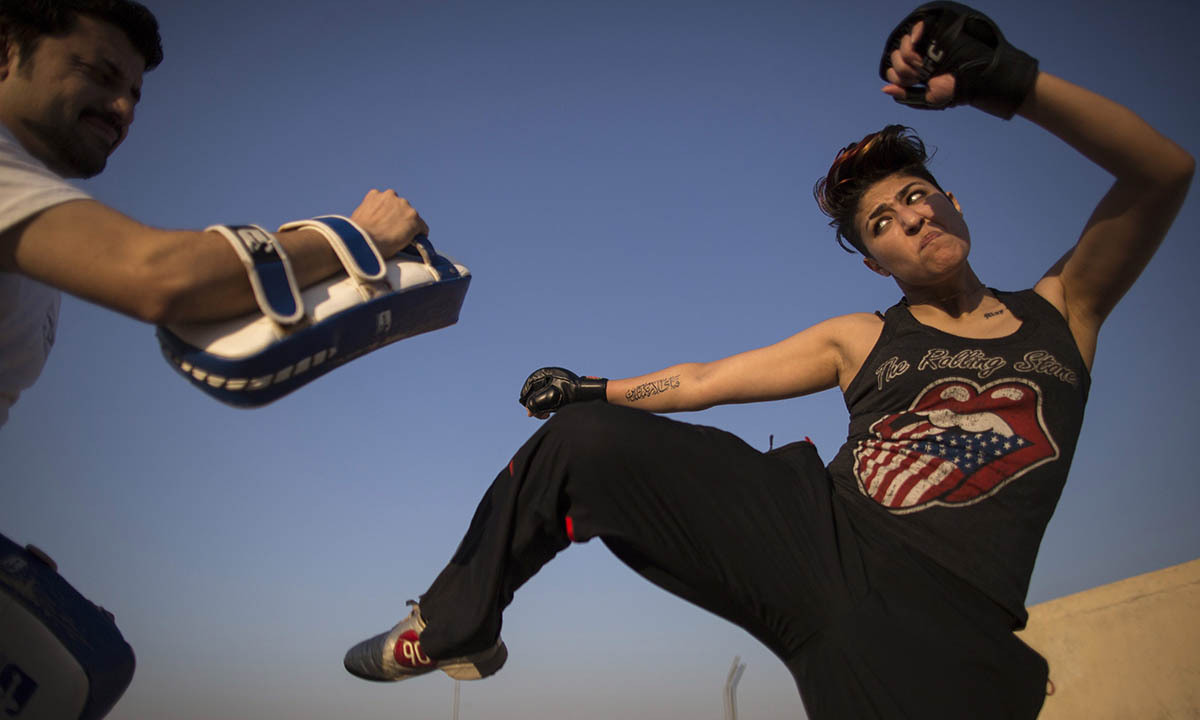 Zahra Afridi (R) kicks a punching bag during a kickboxing training session at her home in Islamabad February 10, 2014.