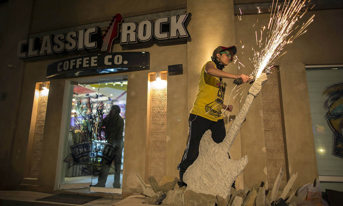 Interior designer Afridi uses a circular saw as she sculpts a stone guitar outside the Classic Rock Coffee cafe in Islamabad March 8, 2014. Afridi runs her own interior design company.