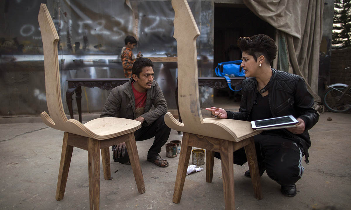 Zahra Afridi (L) talks to a carpenter at a workshop on the outskirts of Islamabad February 10, 2014.