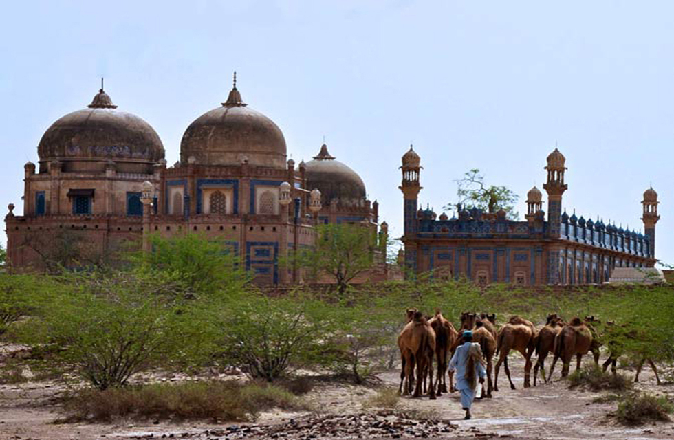 A camel herder leads his camels through the front of the royal graveyard of the Abbasi family near Derawar Fort, Bahawalpur. Photo by Madeeha Syed