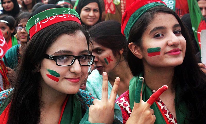 Women supporters of Pakistan Tehreek-i-Insaf showing victory sign during public gathering of PTI near Mazar-e-Quaid on Sunday.— Photo by Online